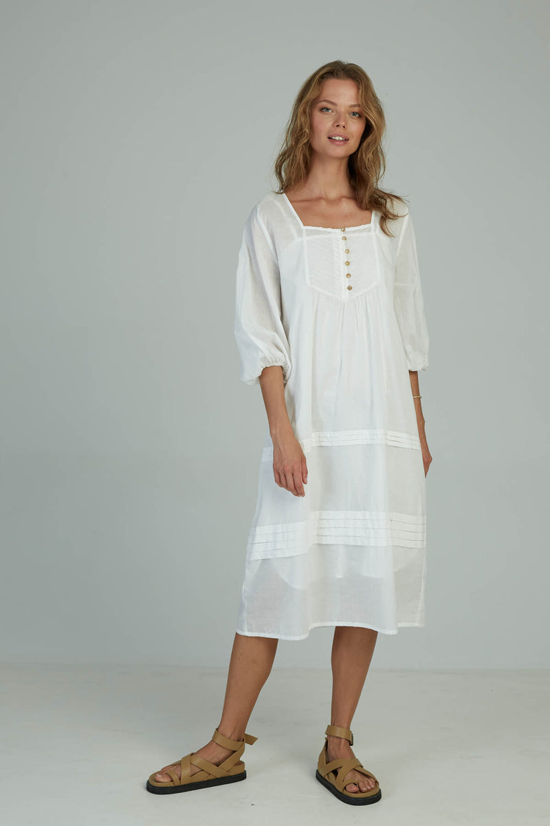 A woman in a romantic summer cotton white dress by Lilya