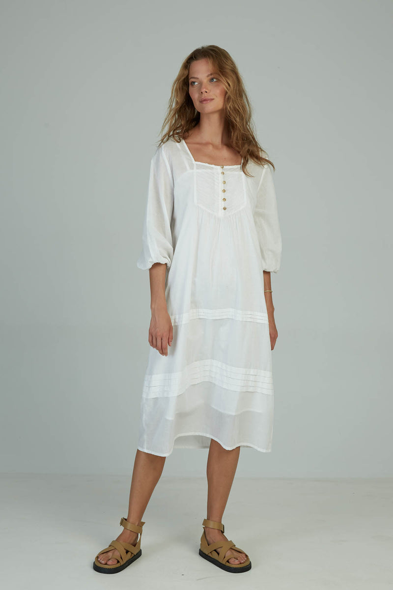 A woman wearing a romantic summer white dress with pintucks by Lilya