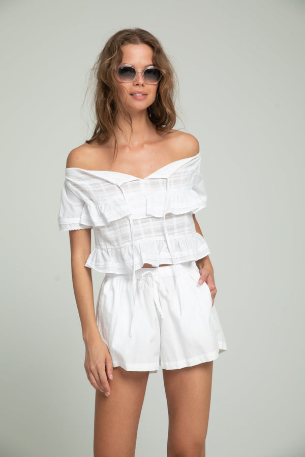 A woman wearing white cotton shorts and off shoulder white top by Lilya