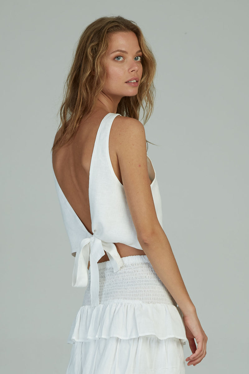 A woman wearing a tie back white linen top by Lilya for summer