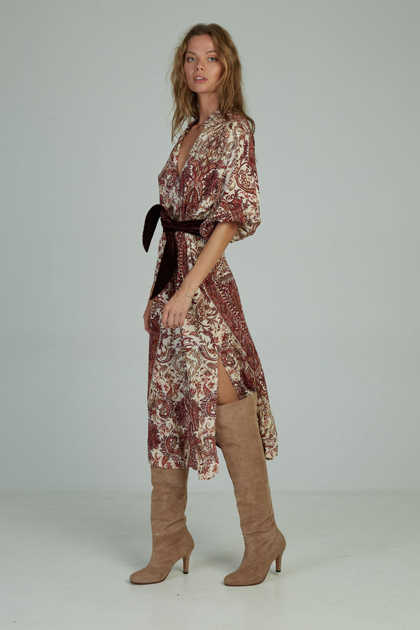 A woman in a paisley maxi dress by Lilya