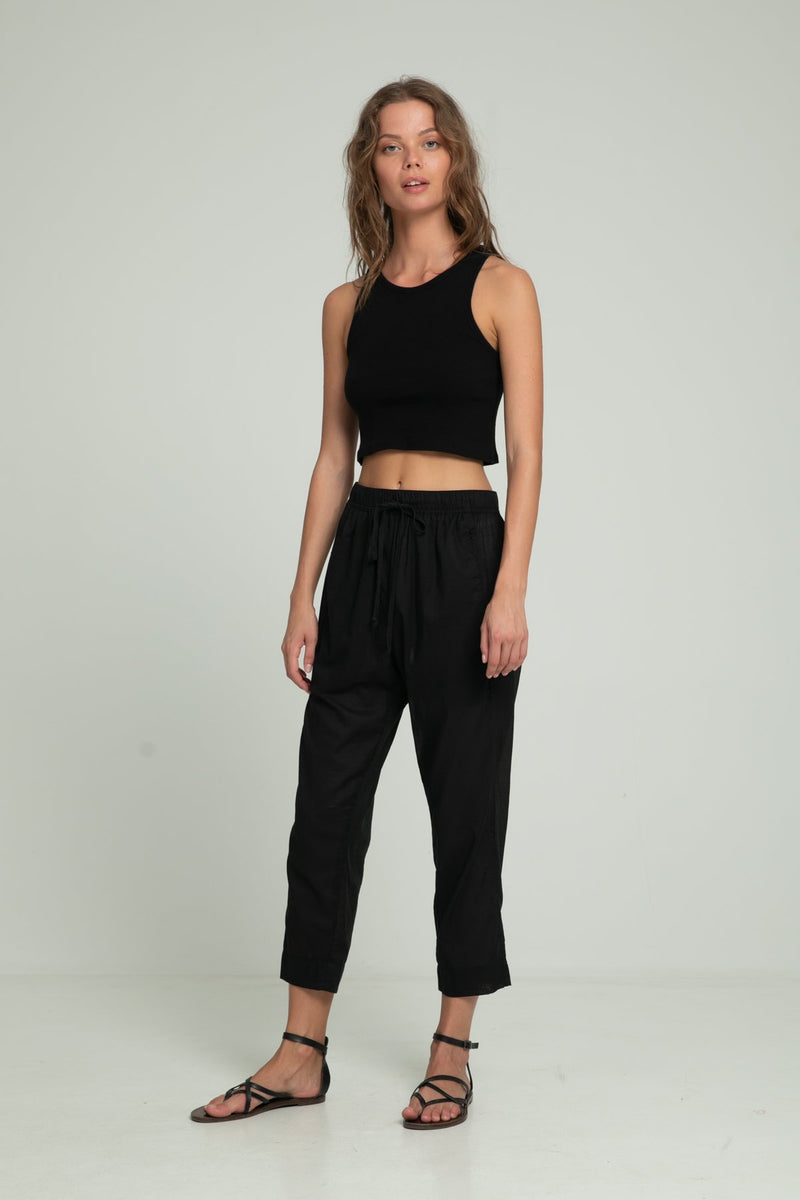 A woman in loose fit black cotton pants and black crop top by Lilya