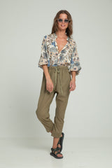 A woman wearing cotton khaki pants and a floral blouse by Lilya