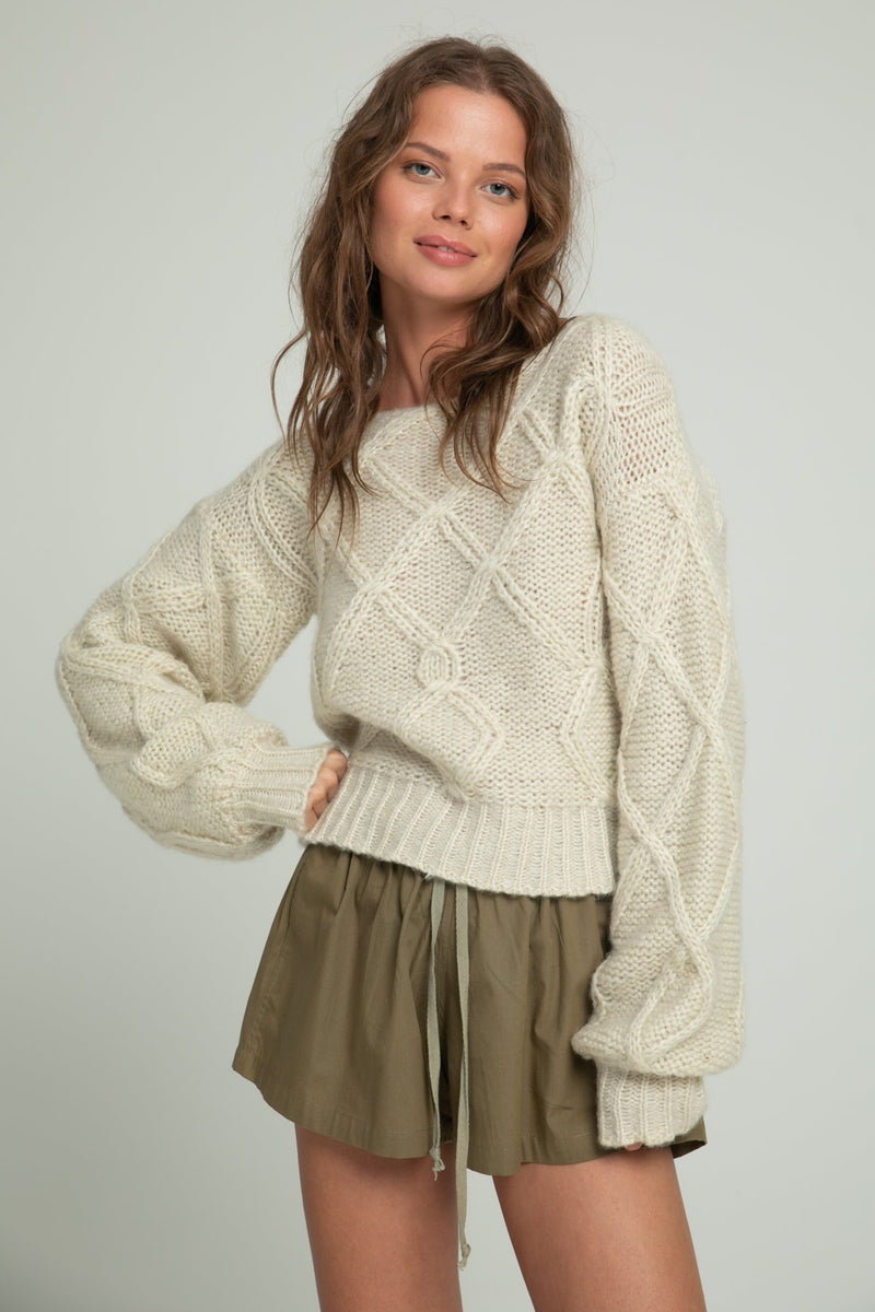 A woman in a white knitted sweater and khaki cotton shorts by Lilya