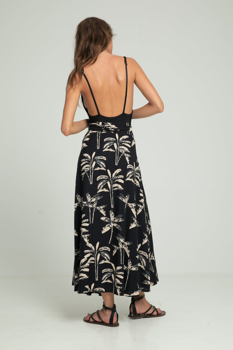 A woman wearing a palm print wrap around skirt by Lilya