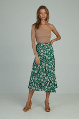 A woman in a green floral wrap skirt by Lilya