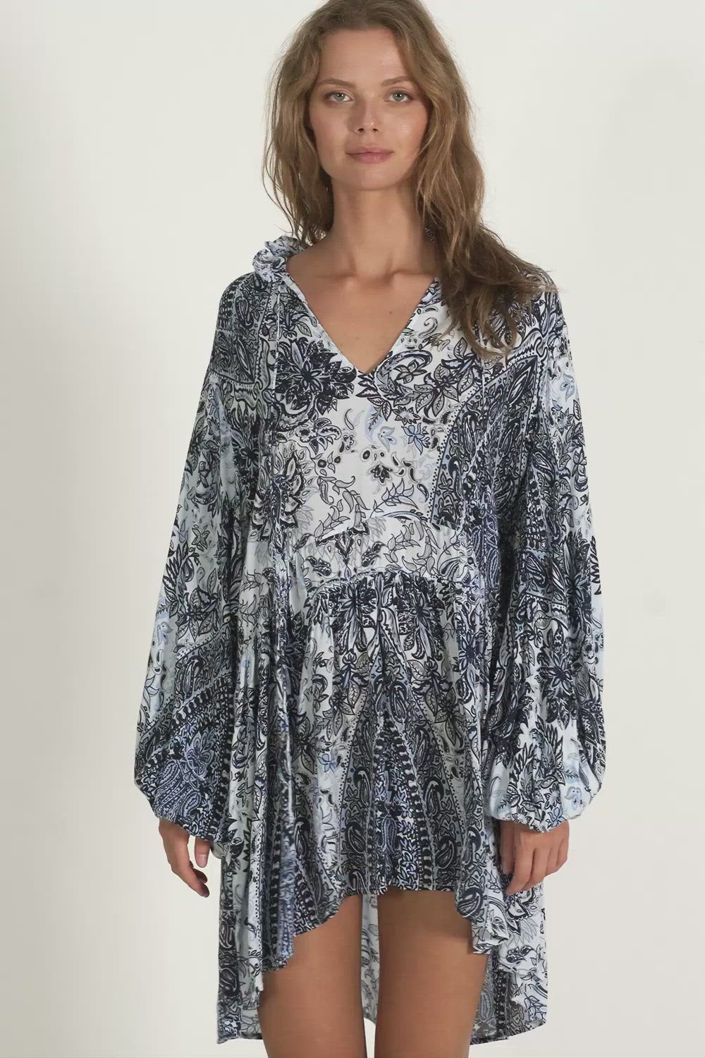 A woman wearing a paisley mini dress by Lilya for winter