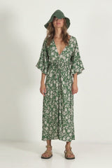 A woman in a long sleeve floral maxi wrap dress for winter by Lilya