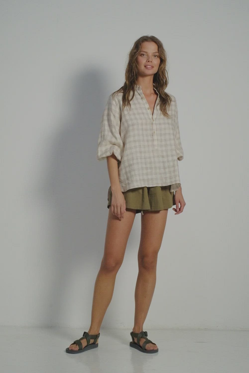 A woman wearing a summer look by Lilya: linen check blouse and khaki shorts