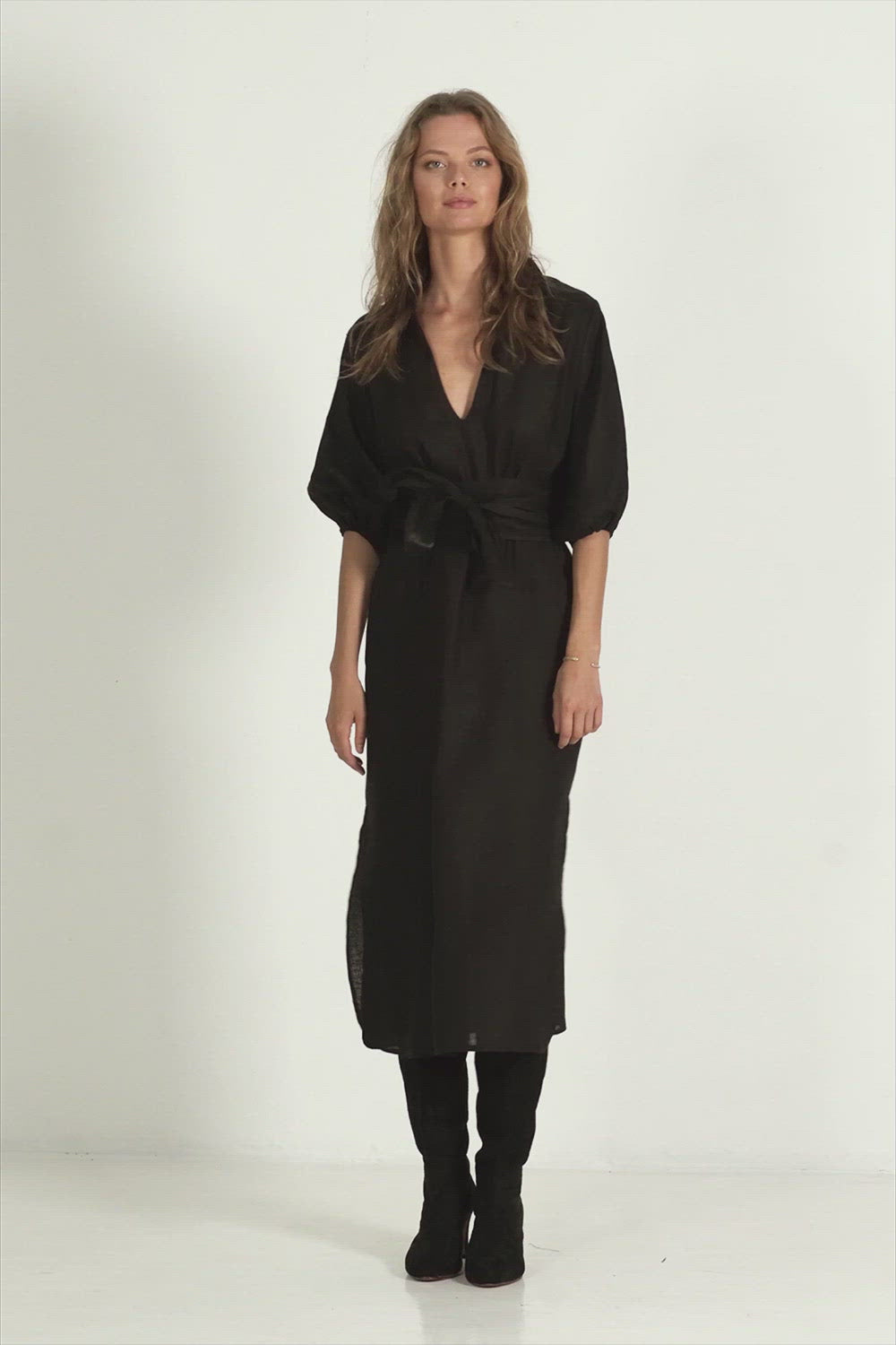 A woman in a trans seasonal black linen maxi dress with balloon sleeves by Lilya