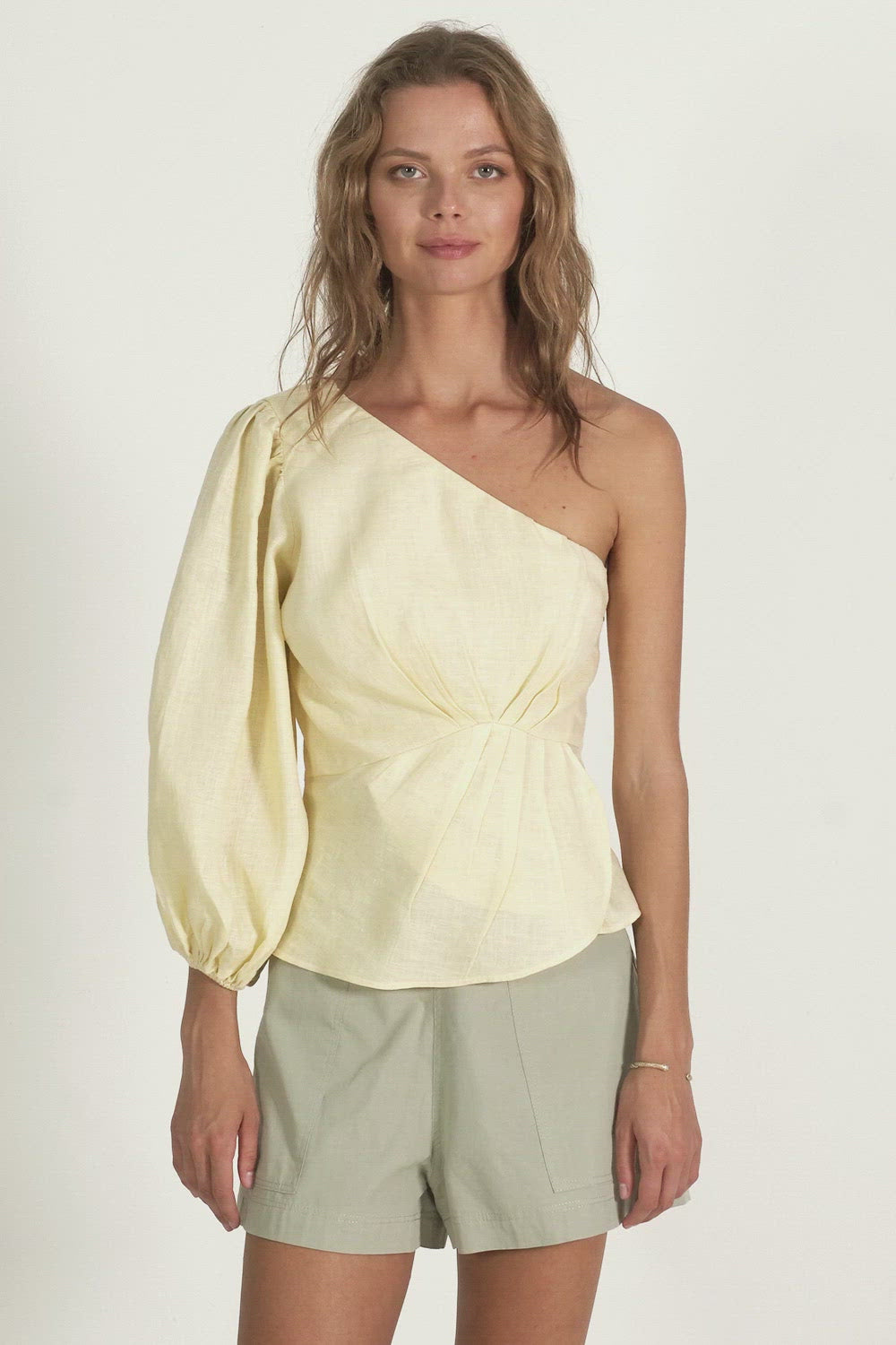 A woman wearing a summer one shoulder top made by Lilya