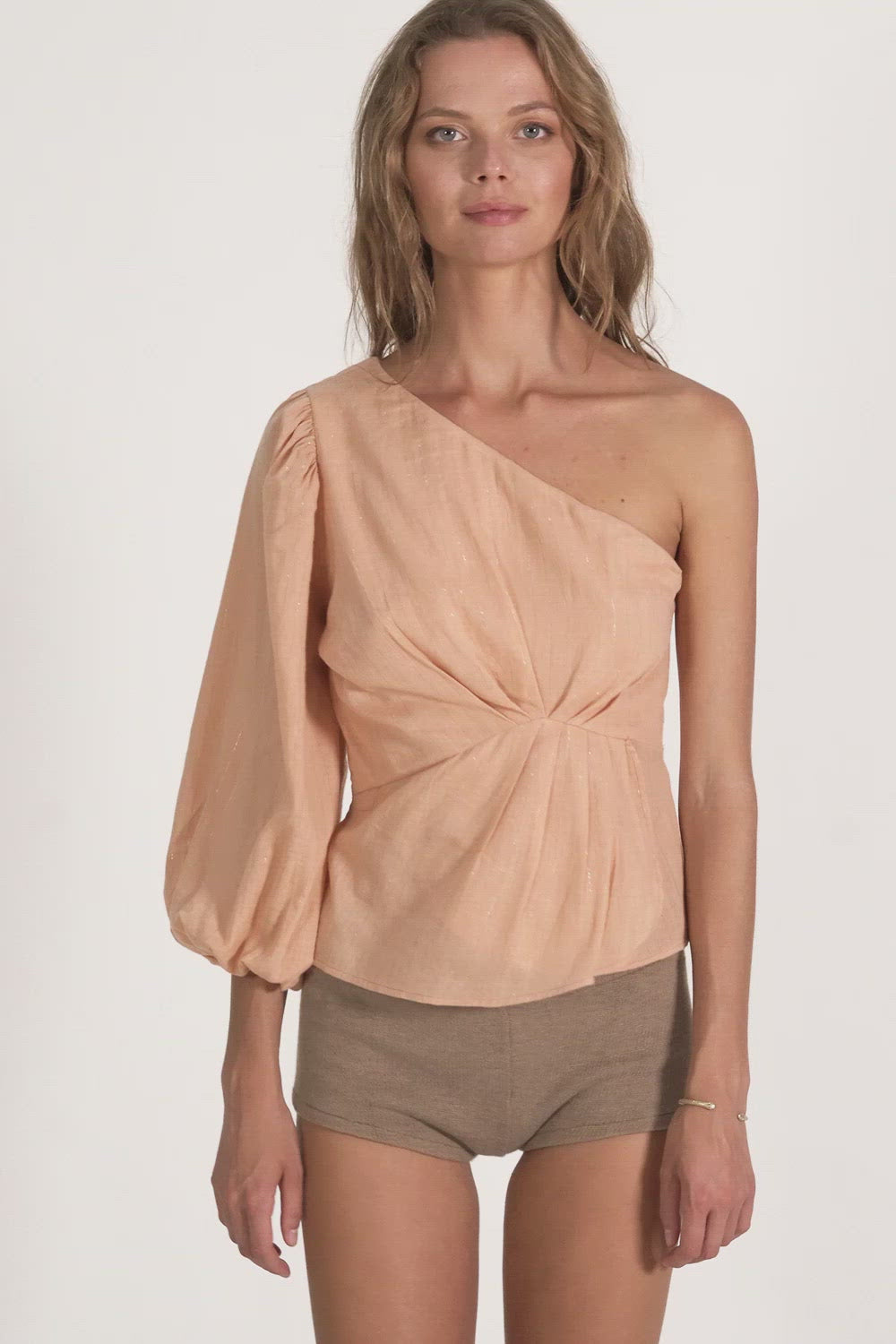 A woman in an elegant one shoulder top by Lilya in Australia