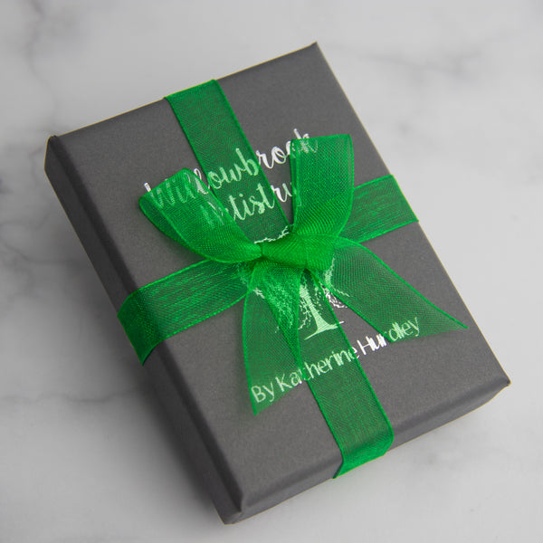 Charcoal grey gift box with silver print and green ribbon