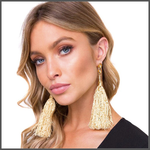 gold drop earrings with a shimmering long cotton tassels on girl model