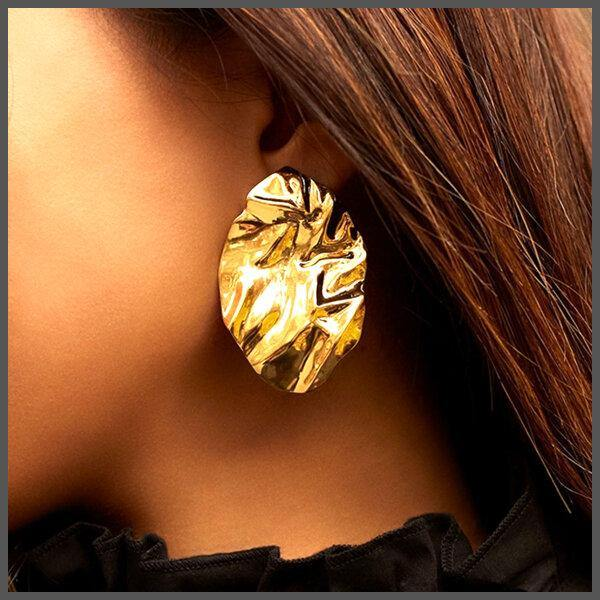 dramatic large gold crumpled statement earrings on girl models ear