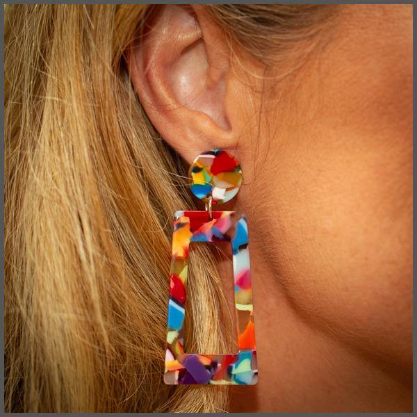 rainbow coloured resin acetate front facing rectangle shape earrings with a front facing circle post on model girl ear