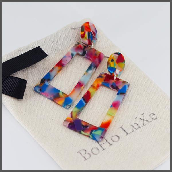 rainbow coloured resin acetate front facing rectangle shape earrings with a front facing circle post on boho luxe gift bag