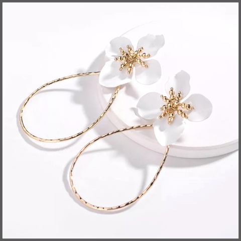 gold earrings with an exaggerated loop with a white flower motif and gold hand beaded centre