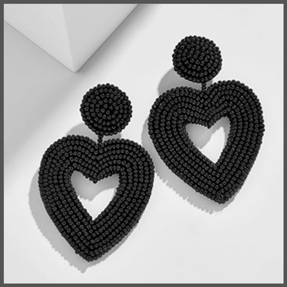black hand beaded drop earrings in the shape of a heart