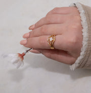 Jewellery hand model wearing 18k gold plated ring stacker ring set with moonstone and mini cz
