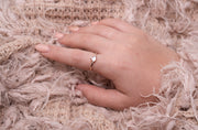 Jewellery hand model wearing 18k rose gold plated ring with natural white moonstone centre surrounded by cz nano stones