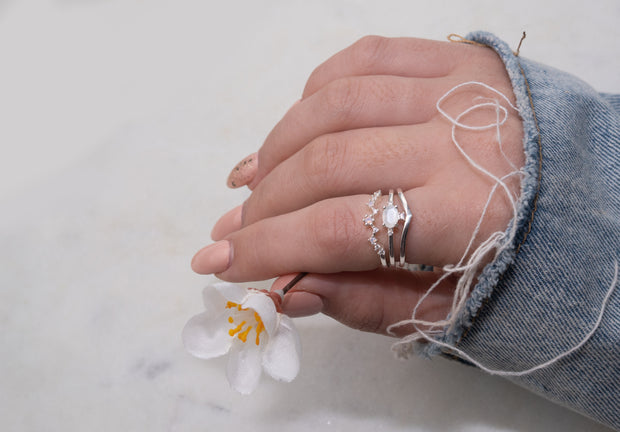 Jewellery hand model wearing Silver ring stacking ring set with moonstone and opal pink nano