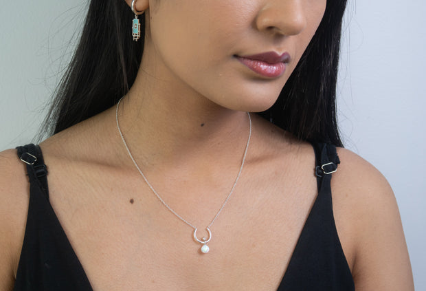 Fashion model wearing Sterling silver horseshoe necklace with simulated opal pendant on model collarbone