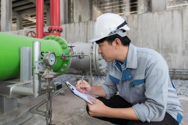 worker checking pressure on descaled pipe