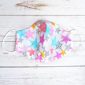 white cotton face mask with filter pocket printed with pink, gold and blue stars