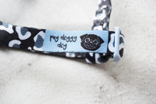 Load image into Gallery viewer, black and white leopard print dog strap harness with blue logo