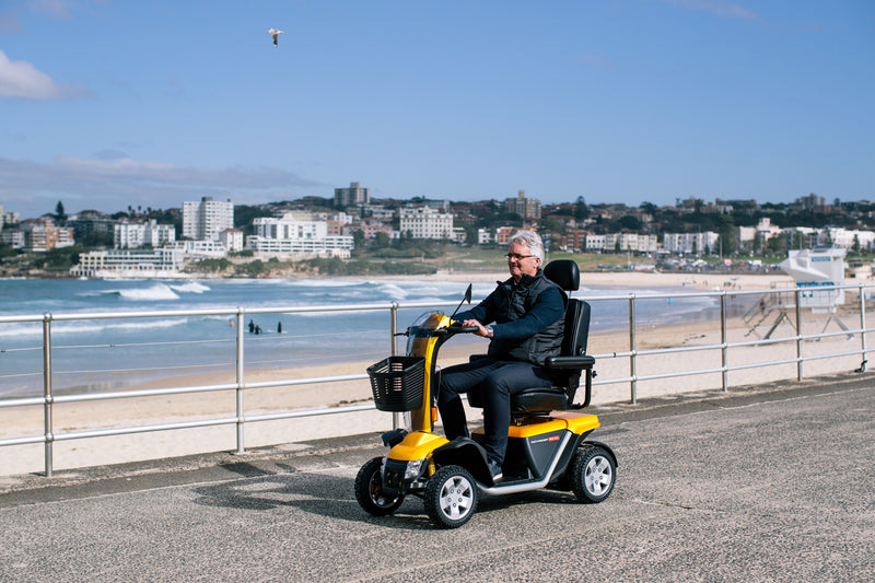 Old man riding Pride Mobility Australia Black Gold Scooter