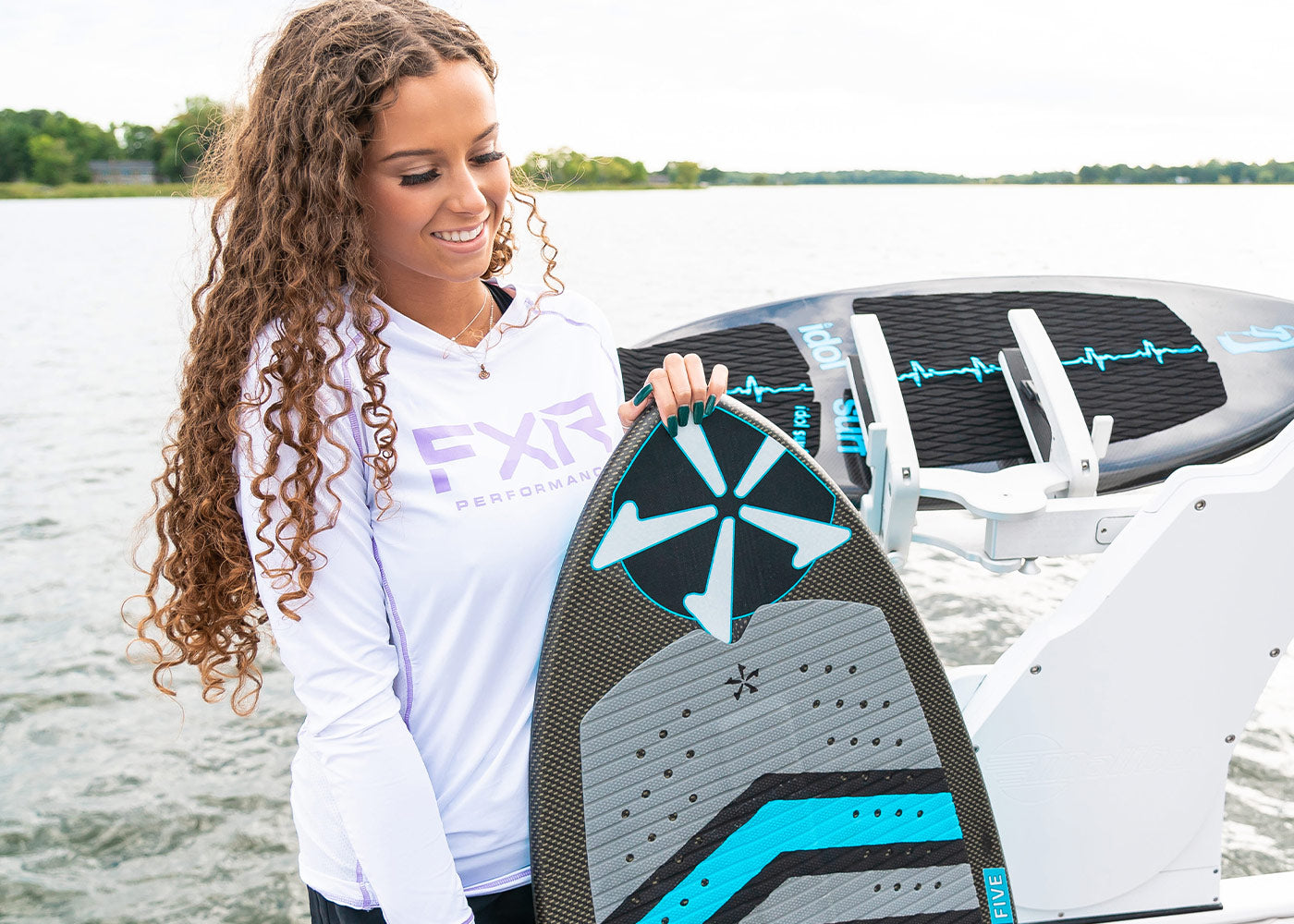 A woman wearing FXR's white and lilac Attack UPF longsleeve holding a grey and blue wakesurf board.