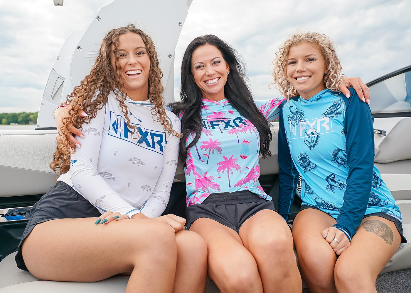 Three women on a boat enjoying the day on a wakeboard boat dressed in FXR's new UPF 50+ performance pullover pieces.