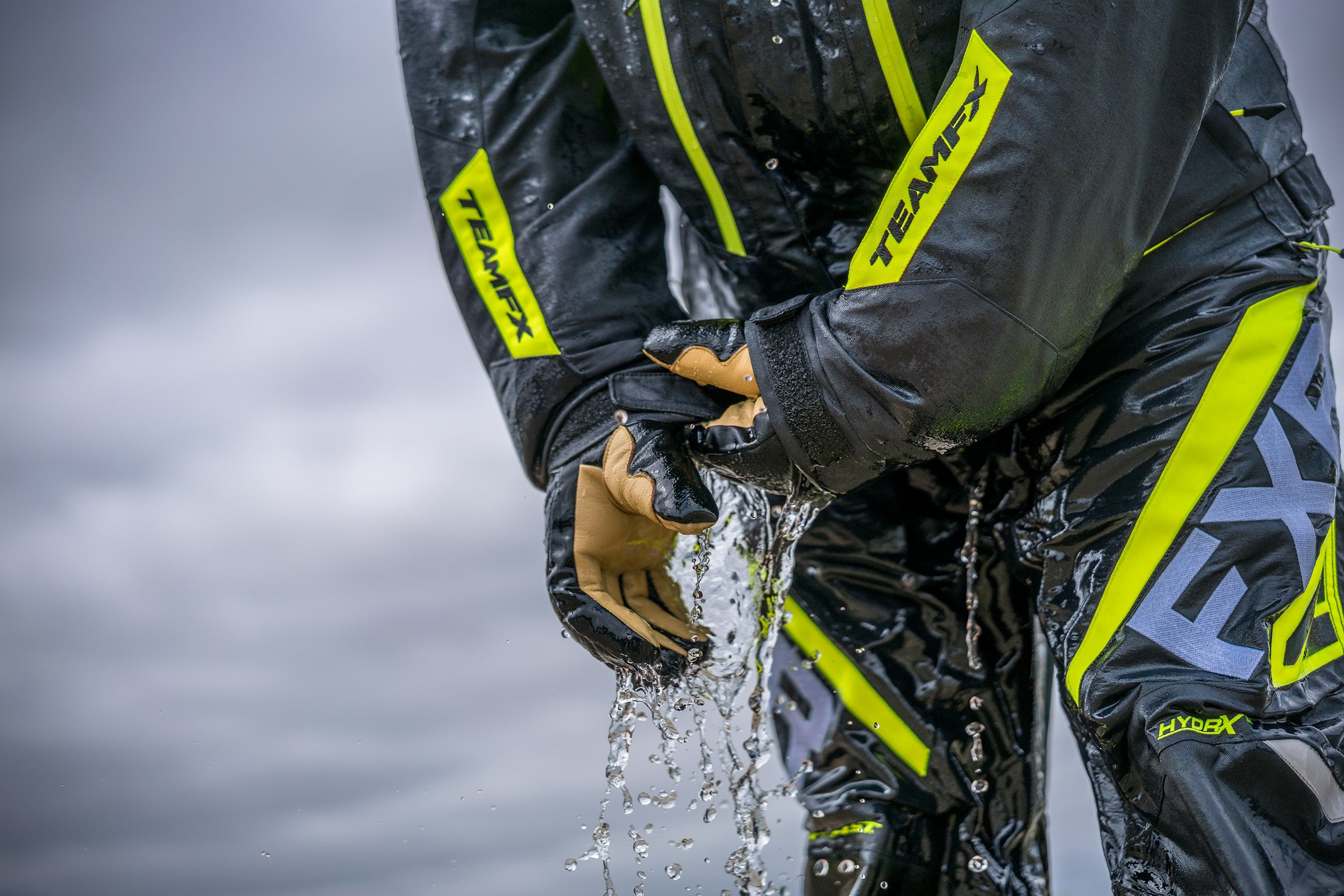 An image of a guy in FXR's F.A.S.T suit demonstrating the rapid drainage feature