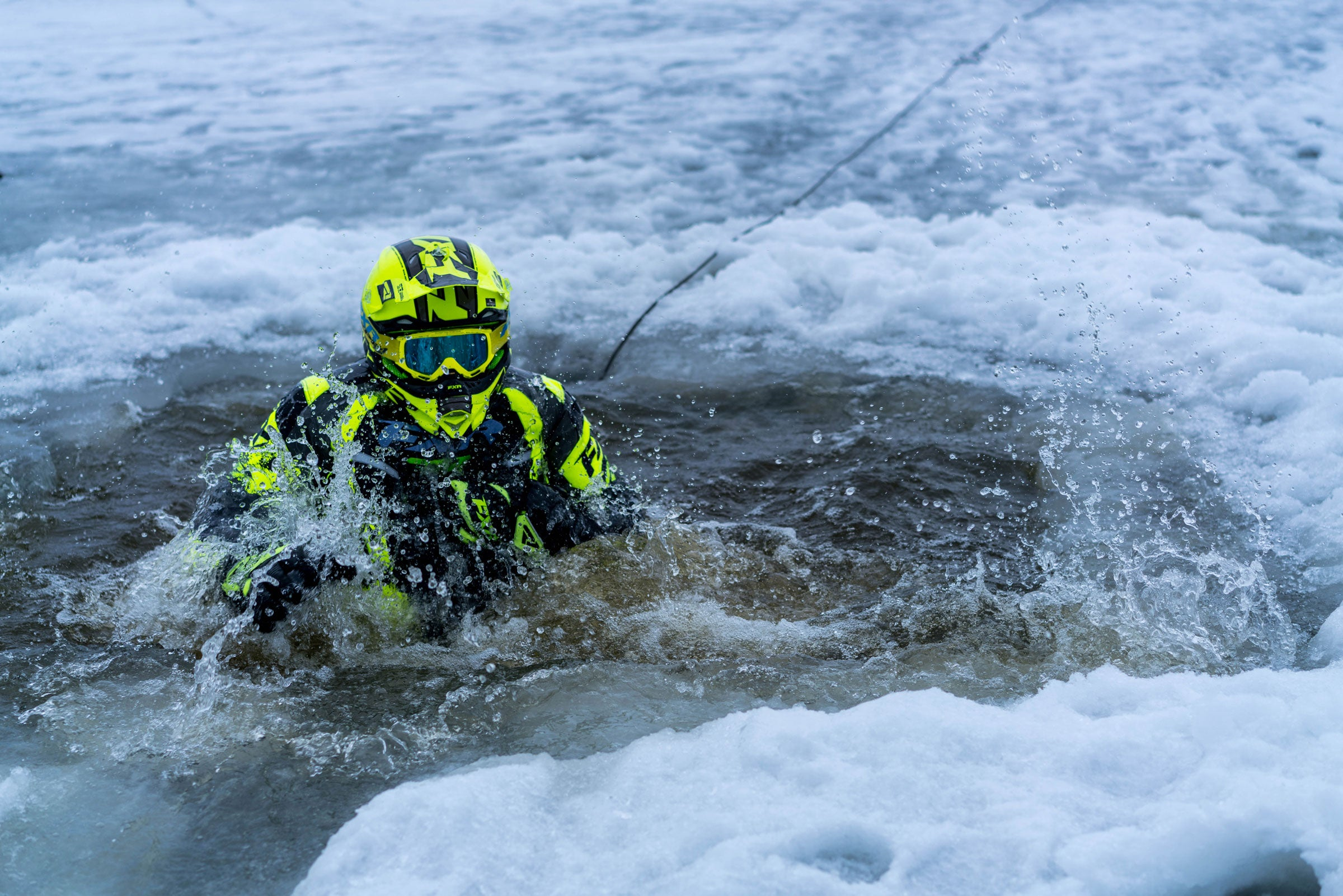An image of a guy in FXR's F.A.S.T suit demonstrating the floatation assist feature