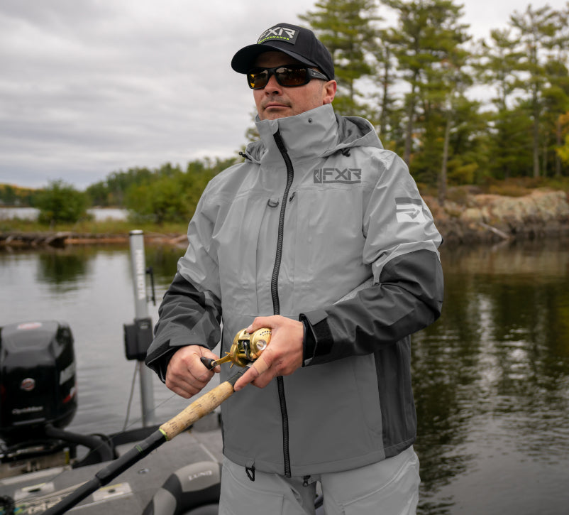 Image of a guy out musky fishing, wearing FXR's men's grey charcoal Vapor Pro Tri-laminate Jacket.