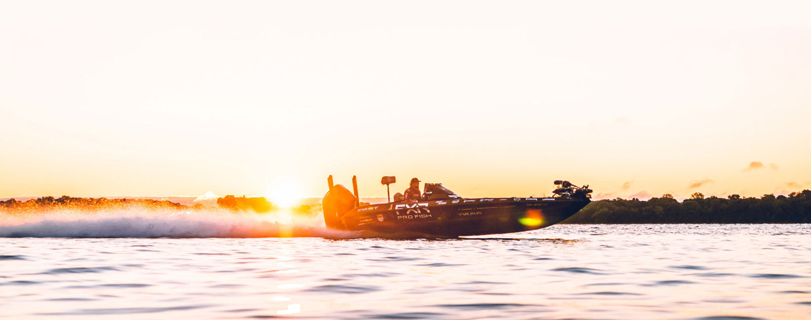 Image of a custom wrapped Pro Fish Vexus bass boat on plane racing across a lake with a sunset in the distance.