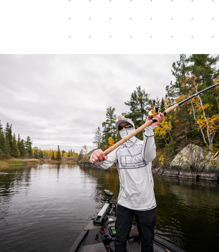 Image of a man musky fishing in FXR's grey textured camo Tournament Pro Hybrid UPF pullover hoodie.