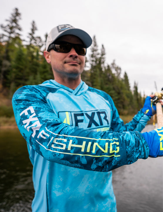 Image of a man out fishing in his FXR's slate blue camo Derby UPF pullover hoodie.