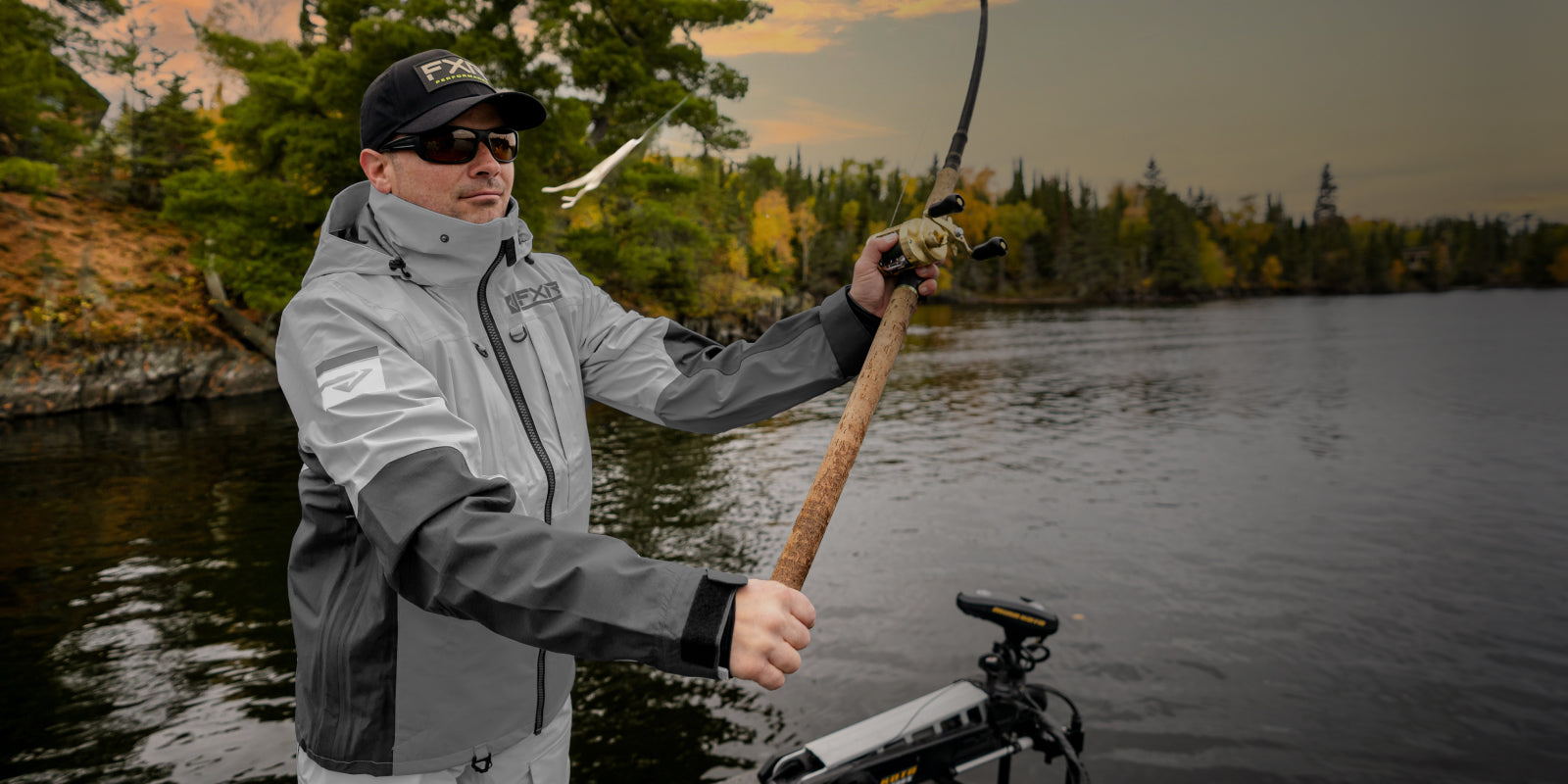 Image of a man musky fishing in FXR's men's grey charcoal Tri-laminate jacket.