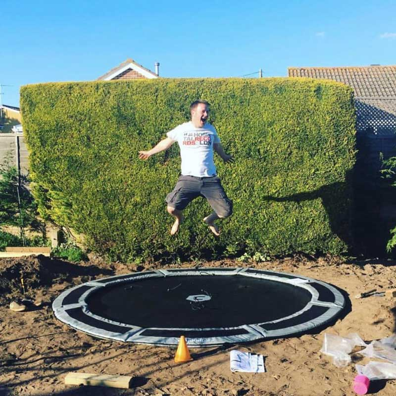 happy man on capital in-ground trampoline