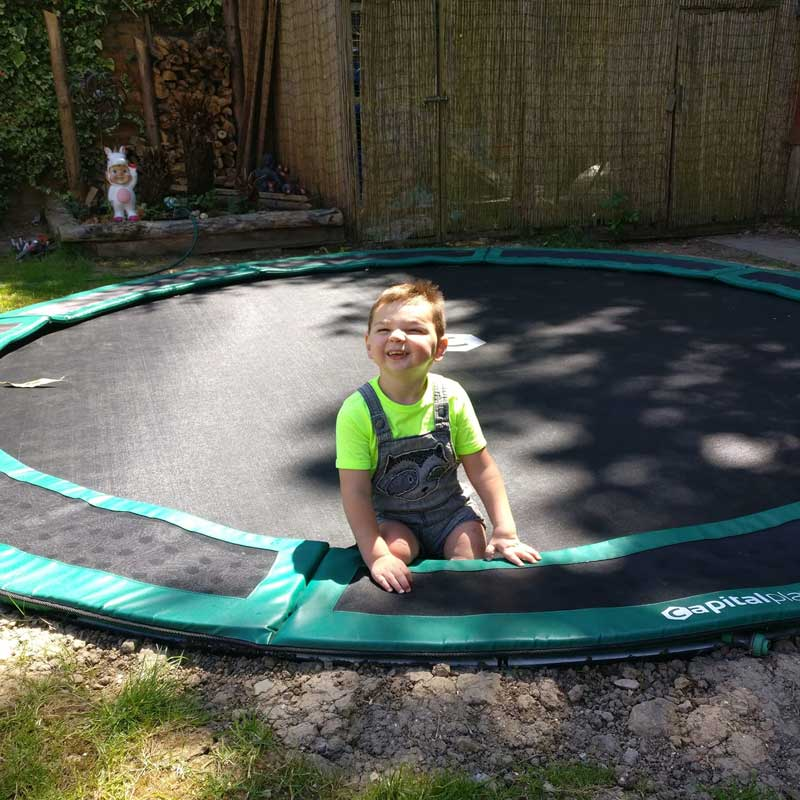 little boy on in-ground trampoline