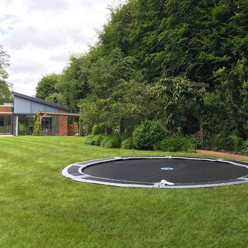 Large 12ft in-ground trampoline in lawn
