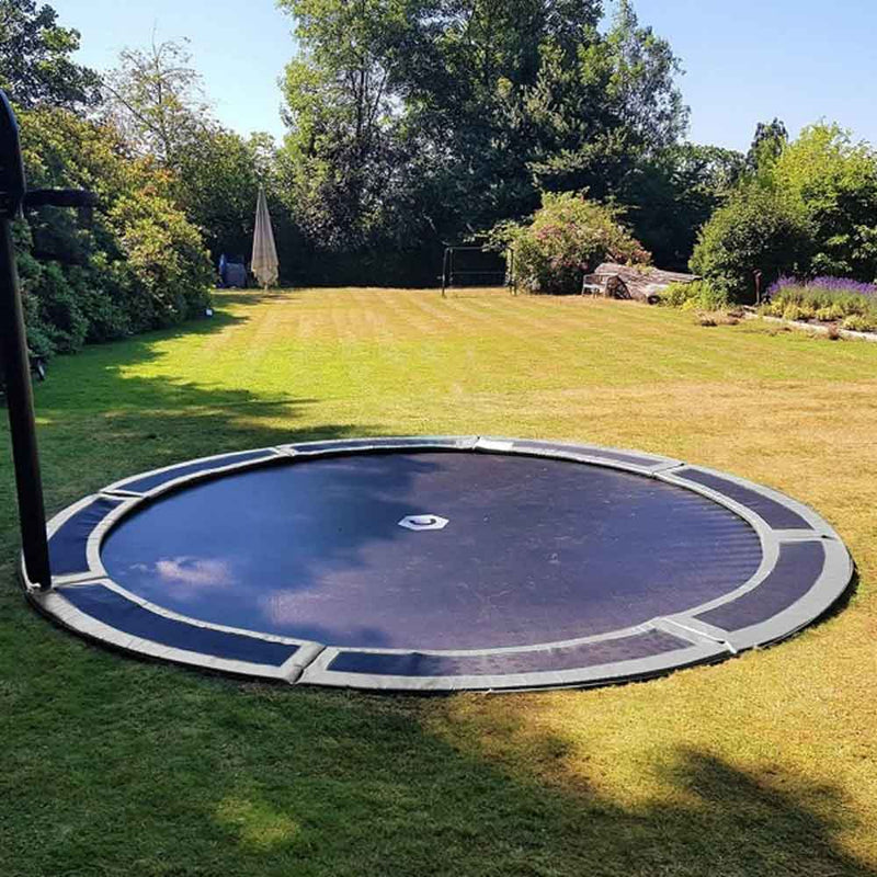Large sunken trampoline in lawned garden
