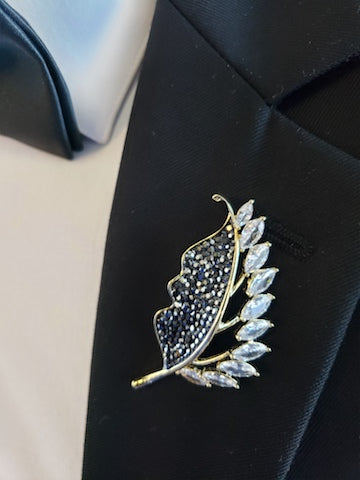 black lapel pin and black broche
