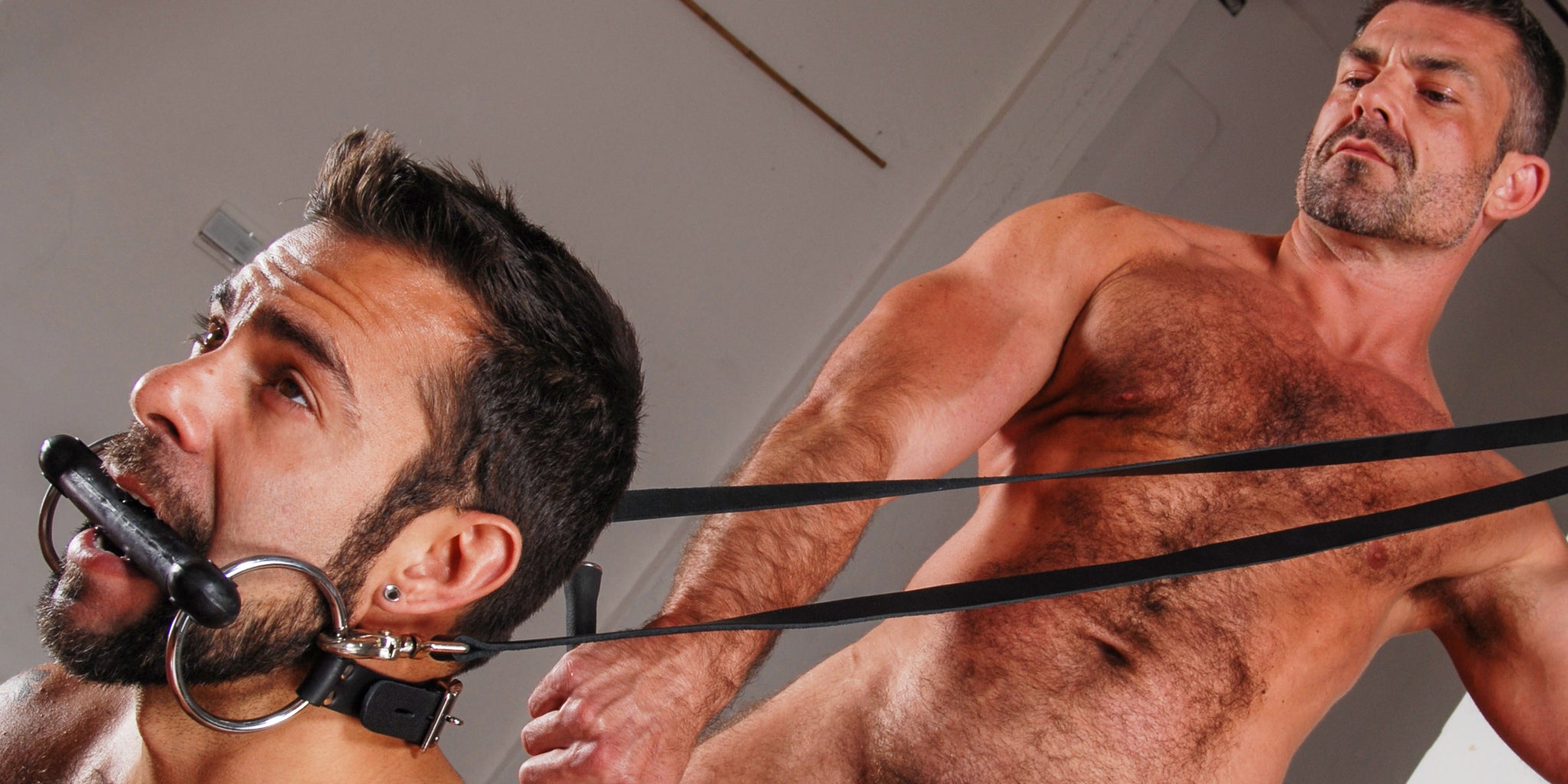 Two men in a bondage scene with one man wearing a rubber bit gag in his mouth and the other man holding black leather leashes. Male Stockroom Sale 2021.