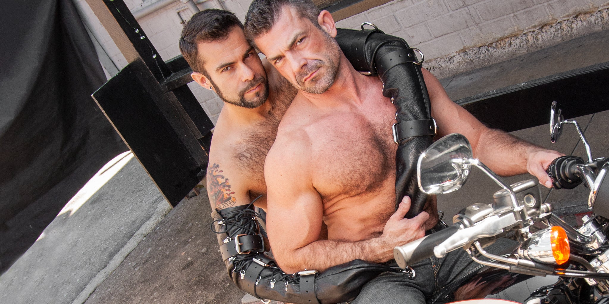 Two gay men holding each other wearing bondage gloves on a motorcycle. Male Stockroom Flash Sale: 20% Off Sitewide with code HEAT21