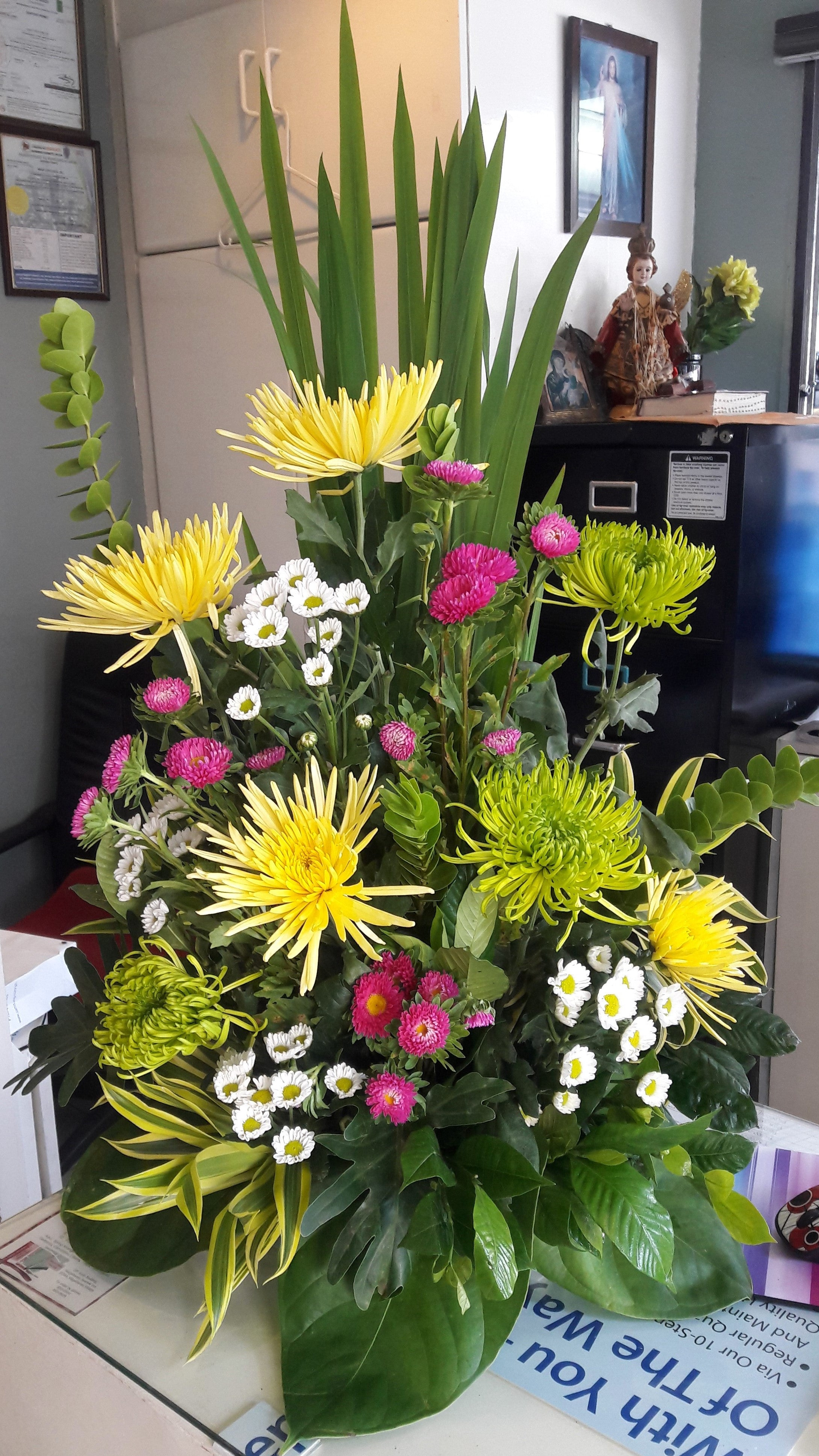 Half faced arrangement with pink, yellow, green, and white chrysanthemums,