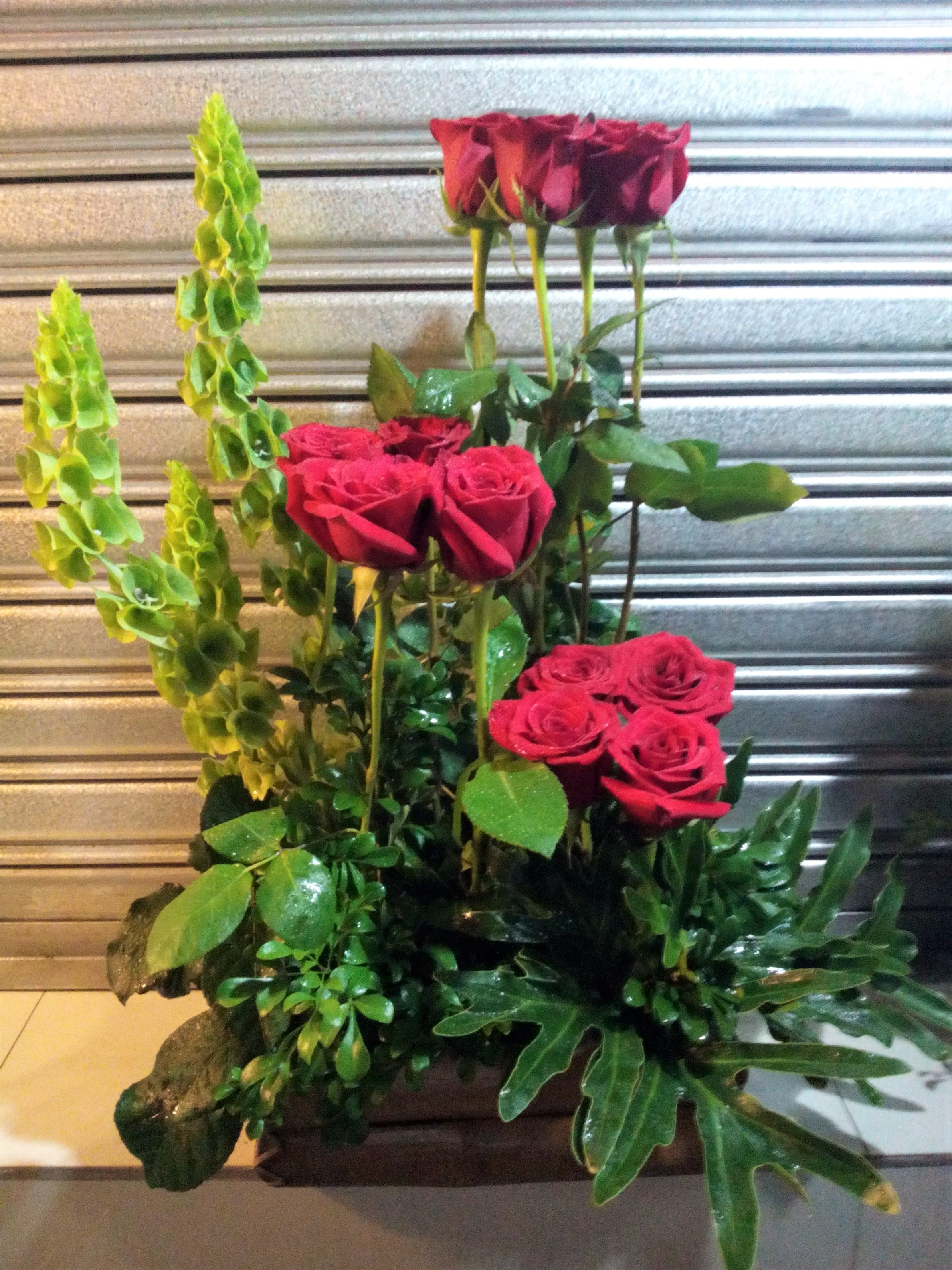 Half faced arrangement with red Holland roses
