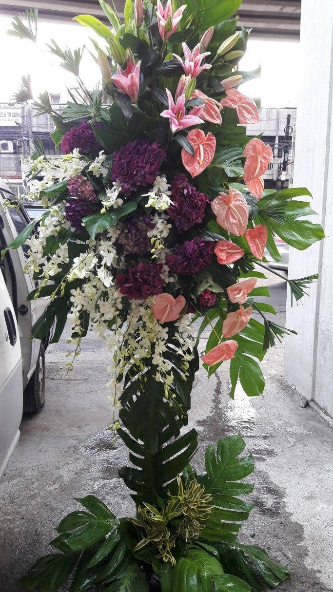standing arrangement with anthuriums, lilies, and hydrangea